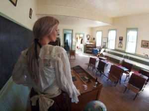A mannequin dressed for the part plays the role of teacher in the old school house.