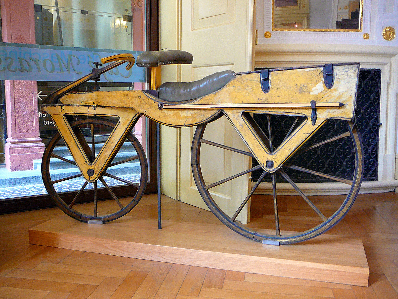 """Draisine, also called Laufmaschine (""""running machine""""), from around 1820. The Laufmaschine was invented by the German Baron Karl von Drais in Mannheim in 1817. Being the first means of transport to make use of the two-wheeler principle, the Laufmaschine is regarded as the archetype of the bicycle. The above Draisine was built with cherry tree wood and softwood. It is displayed at the Kurpfälzisches Museum in Heidelberg, Germany (Inv.-No. GH 98).  (Text and image from WikiMedia and licensed for reuse.)"""