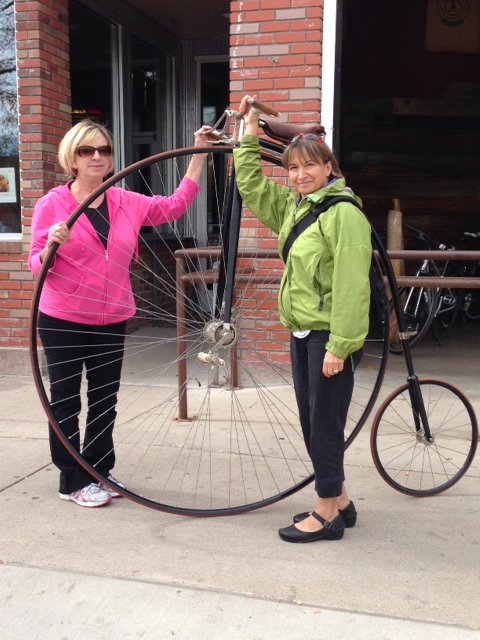 """Laurie Evans (of the Poudre Landmarks Foundation) and Sylvia Cranmer (of Bike Fort Collins) pose with a penny farthing that is part of the Vintage Bike Museum without walls. As the name implies, the """"museum"""" travels about from location to event to another location. This photo was taken in front of Cranknstein before the bicycle was moved to the Masonic Temple for the Time Travelers Ball last autumn that was put on by the Poudre Landmarks Foundation. (Photo taken by Jennifer Beccard.)"""