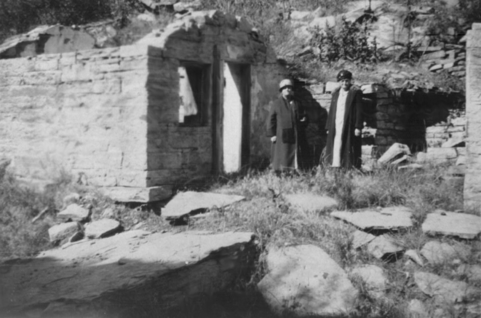 Carolina, probably with Maria, standing by the stone cabin where she had lived in Stout.