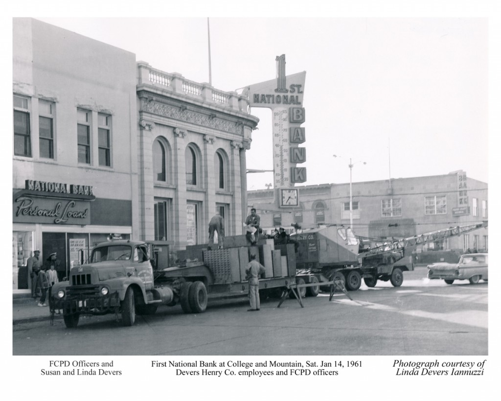 Wide angle shot of the bank building. The truck laden with safety deposit boxes is in front along E. Mountain.