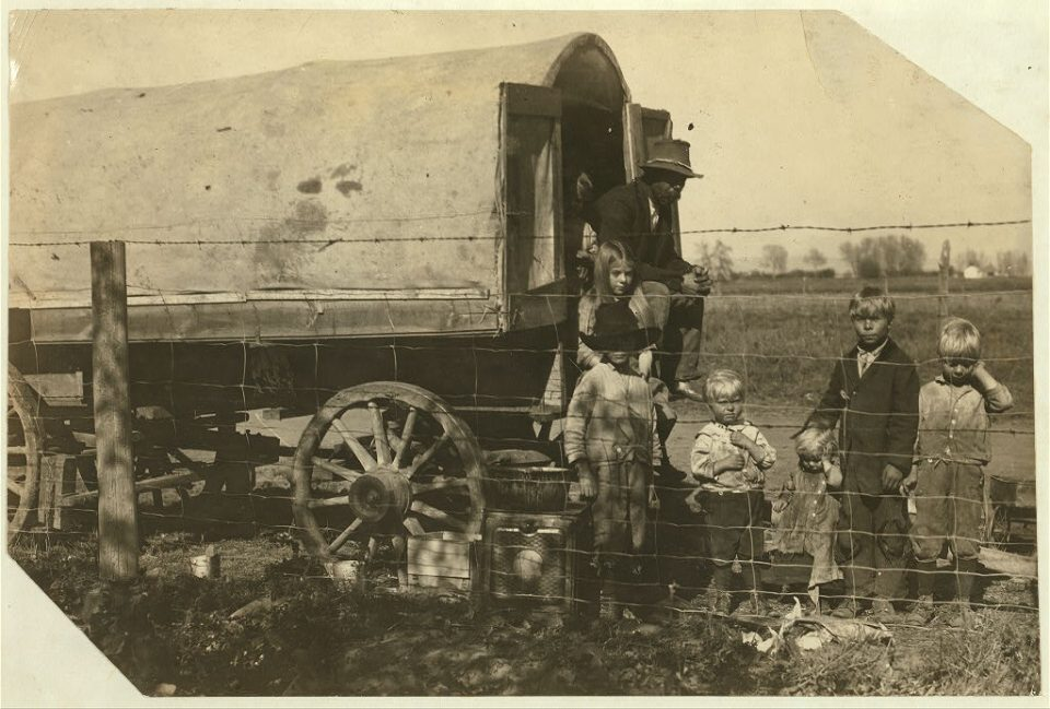"""The caption on this photo from the Library of Congress reads: """"The prairie-wagon home of a family of itinerant beet workers, now camped near Ft. Collins, Colo. Street family. The children 7- 8- 10- and 12 work steadily and I saw the tiny girl pulling beets after sunset on the following Sunday, and they had not yet finished. The father told me """"We got squeezed out of the mountains,"""" one of the neighbors said they has been chased out because they wouldn't send their children to school. Living on the edge of Ft. Collins, they boldly work the children and violate school law. Came from Log Cabin, Colo. Location: Fort Collins [vicinity], Colorado / Photo by Hine, Oct. 30/15."""" (Control #: ncl2004004413/PP)"""