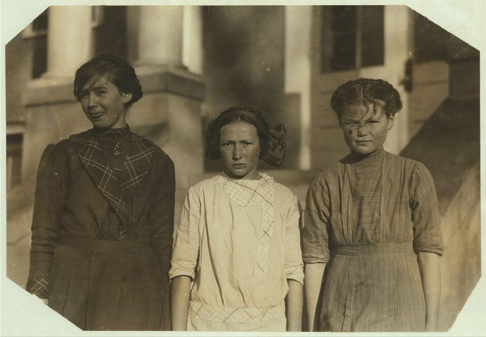 """The caption on this Library of Congress photo reads: """"Girls - one 14 years and two 12 years old in the third grade of the Rockwood Place School. Some children 7 and 8 years old in this grade. Regular age is 8 and 9. Teacher says retardation is due chiefly to beet work."""" Photo taken by Lewis Wickes Hine in 1915."""