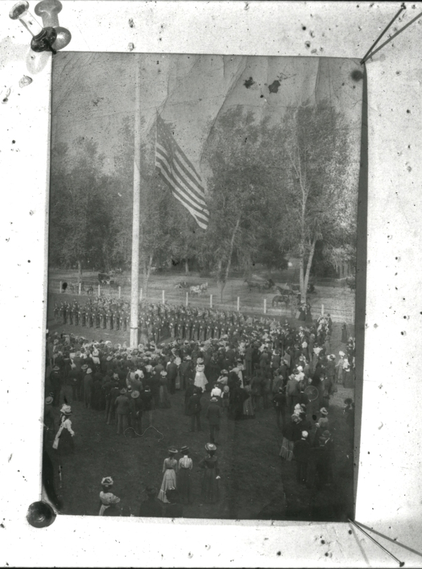 This photo from the Colorado State University Digital Archive (ID UHPCSNP_6744) shows a military event taking place at the flag pole with a crowd of bystanders in Victorian Era attire.
